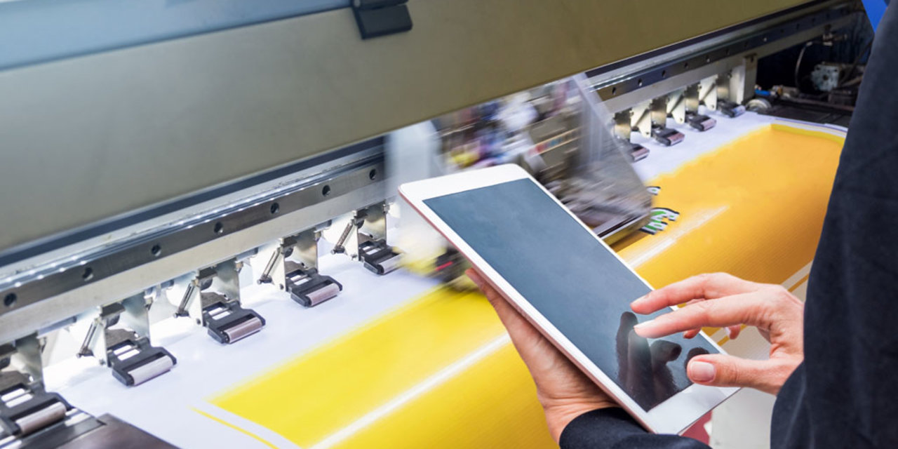 Technician touch control tablet on format inkjet printer during yellow vinyl paper